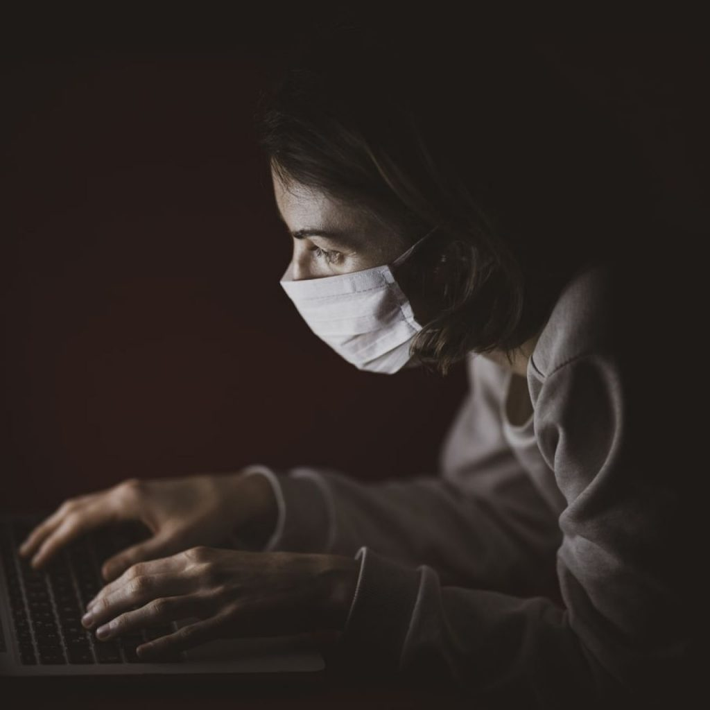 Woman with mask working on her home laptop